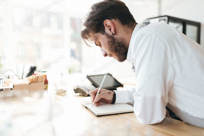 Barista thoughtfully making notes at work in coffee shop