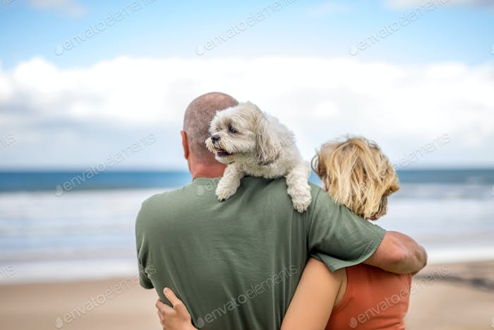 Man and woman hugging and holding a lap-dog on a shoulder