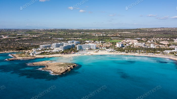 aerial view of touristic town on seashore with blue sky and sea, Cyprus