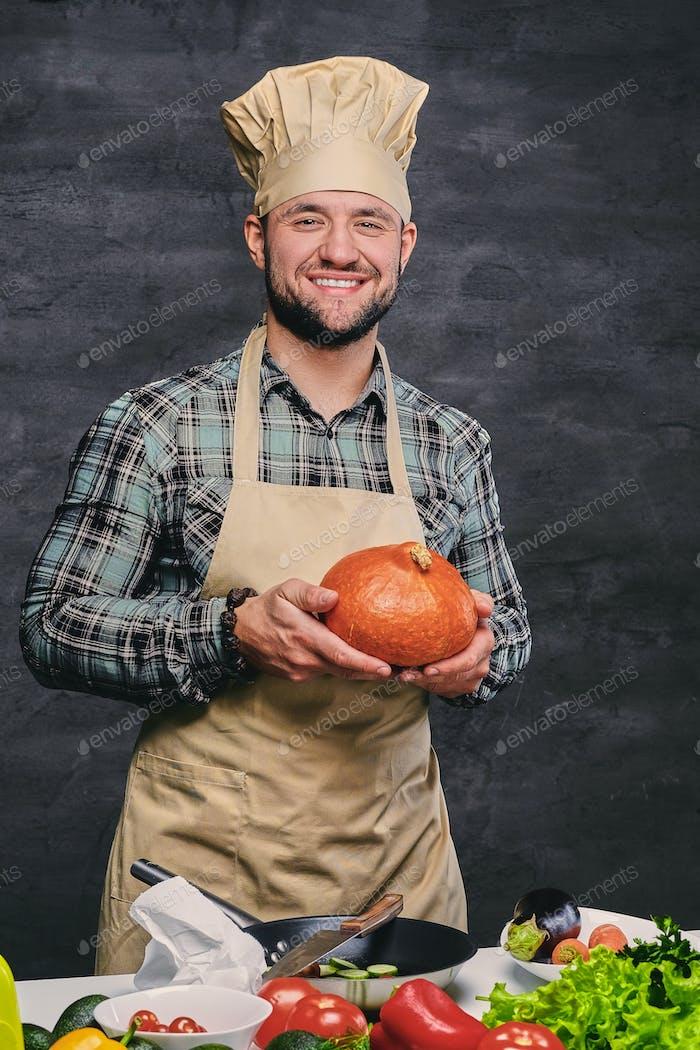 Bärtiger männlicher Koch hält Kürbis.