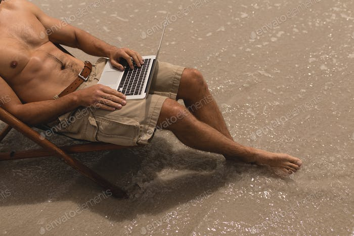 Low section of shirtless young man relaxing on sun lounger and using laptop on beach in the sunshine