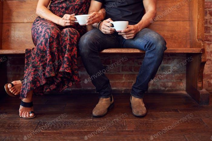 Nahaufnahme auf Füße der paar sitzen auf bank in coffee shop zusammen