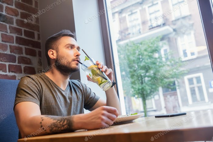 Man sipping cold drink in a restaurant.