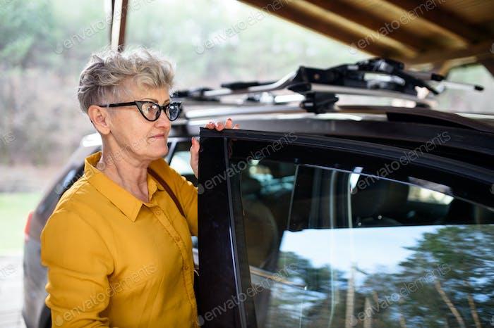 Senior Frau mit Brille stehend im Freien mit dem Auto von Haus