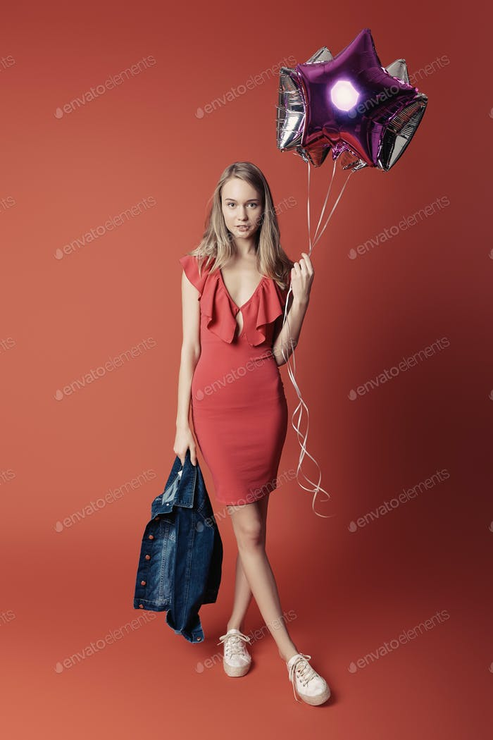 Woman in red dress holding balloons.