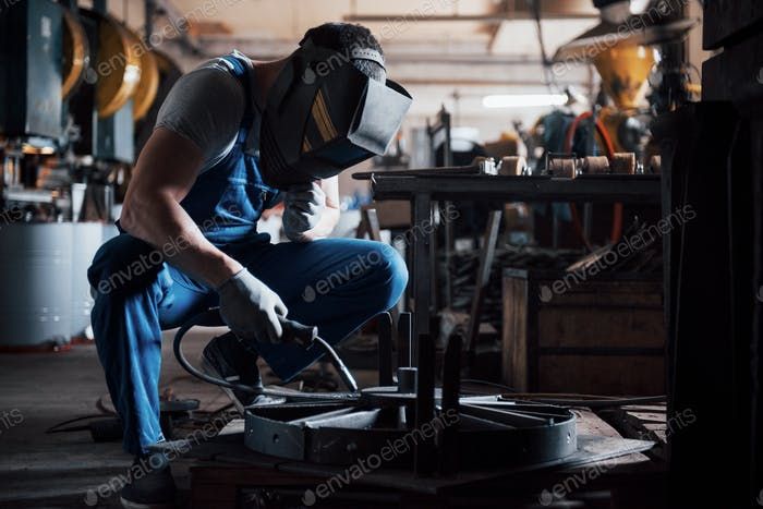 Portrait of a young worker at a large metalworking plant. The welder engineer works in a protective