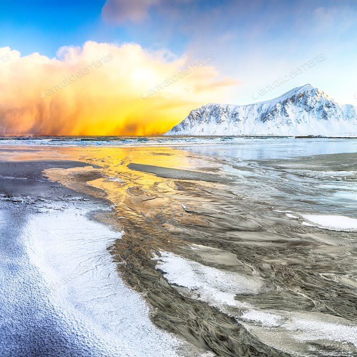 Incredible winter scenery on Skagsanden beach with illuminated clouds during sunrise.
