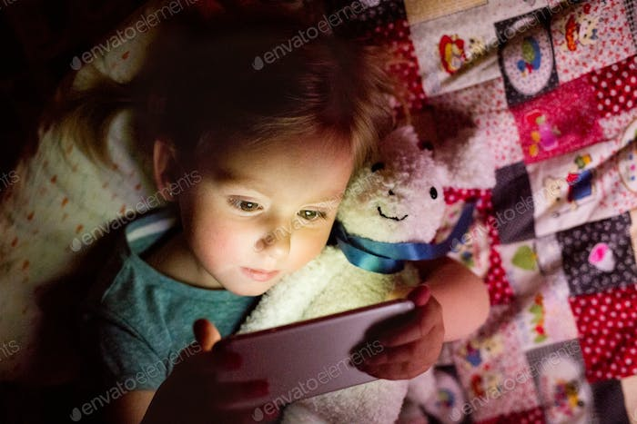 Little girl at home at night watching something on smartphone.