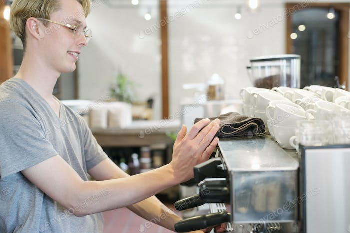 Young blond man with spectacles standing at an espresso machine in a coffee shop.