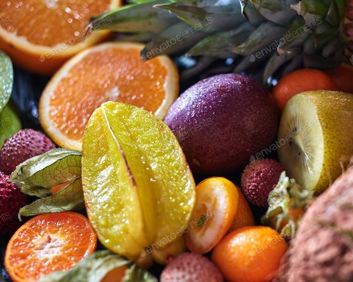 Tropical fresh juicy fruits as a backgraund with carambola, kumquat, passion fruit,, orange halves