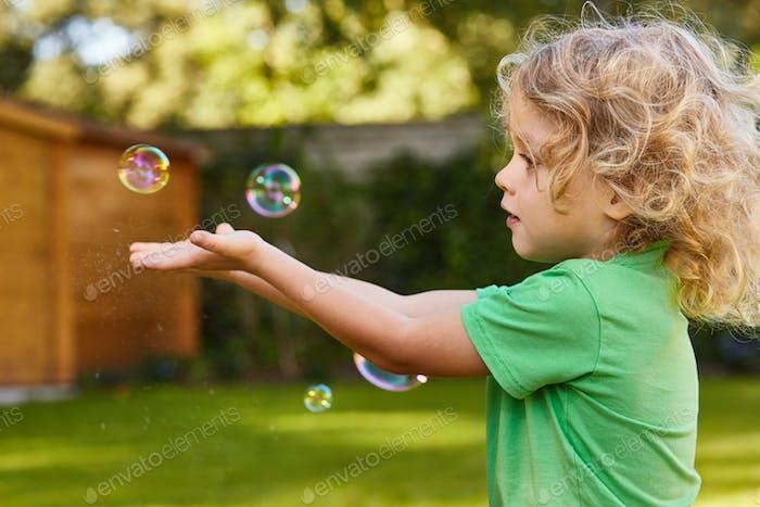 Boy catching soap bubbles