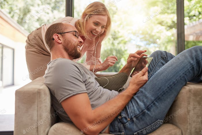 Couple listening to music on a tablet and sharing earphones