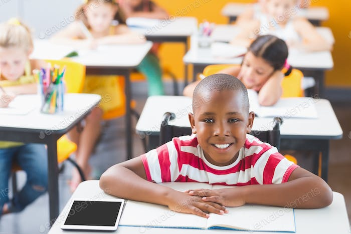Disabled schoolboy smiling in classroom