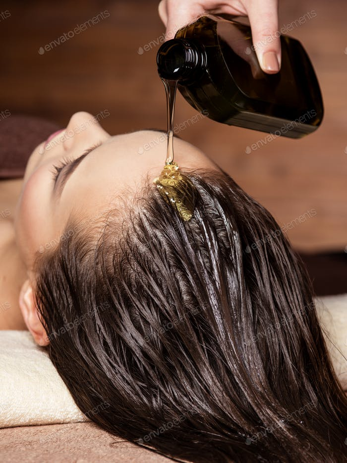 Cosmetologist pours balm for hair on head of  woman. Spa treatme