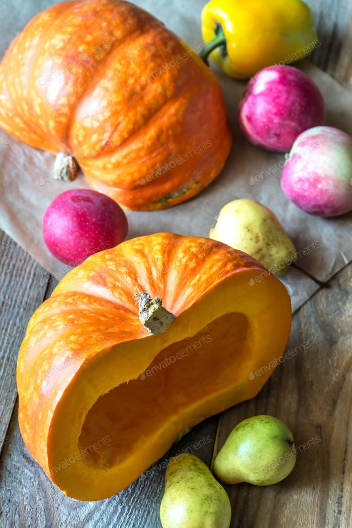 Pumpkin with fruits on the wooden background