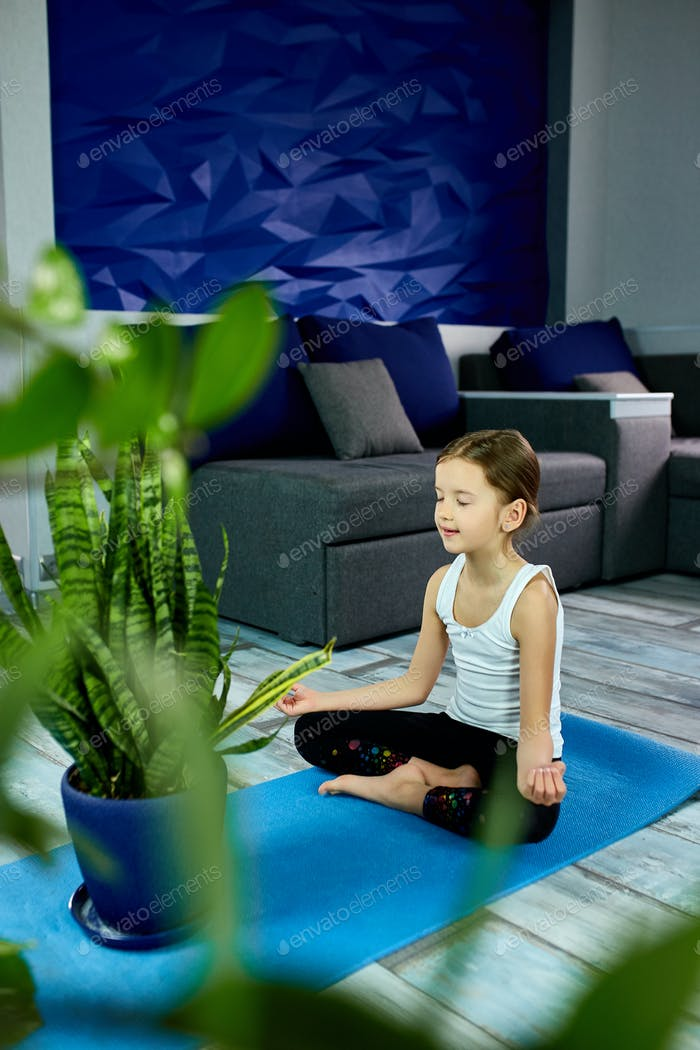 A girl sitting in yoga asana on a blue background.