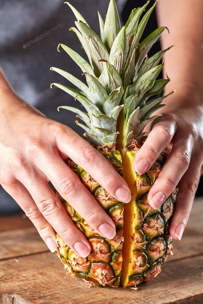Fresh halves of an exotic pineapple hold the girl's hands on a wooden kitchen board. Vitamin