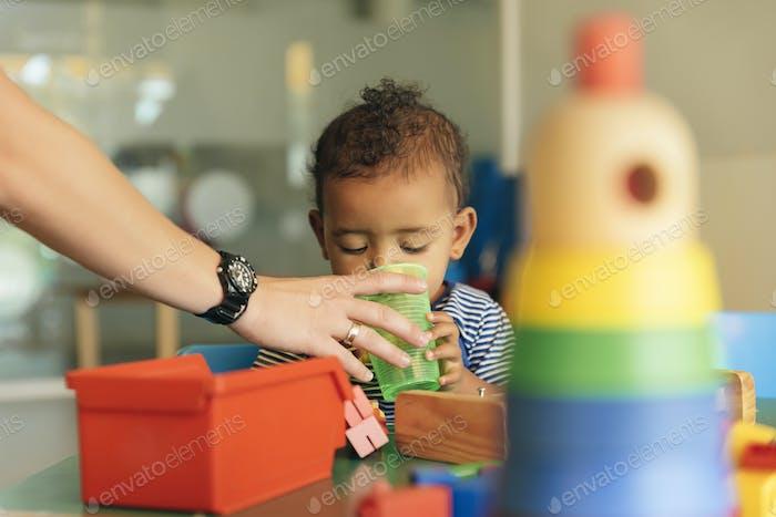 Glückliches Baby Trinkwasser und spielen.