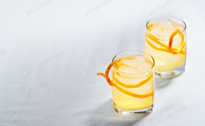 Cool refreshing alcohol cocktail decorated with orange zest