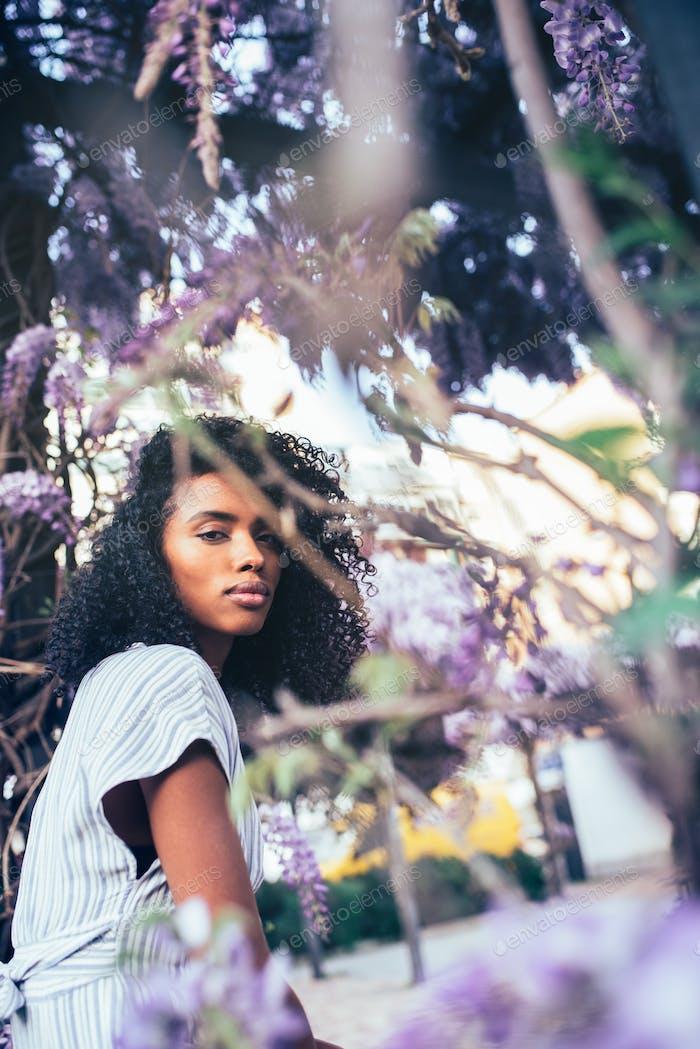Nachdenklich junge schwarze Frau sitzt umgeben von Blumen
