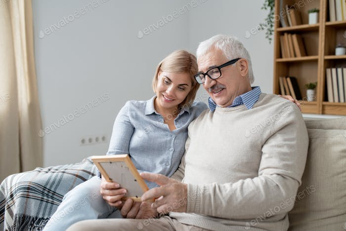 Senior man in casualwear showing his happy young daughter photo in frame