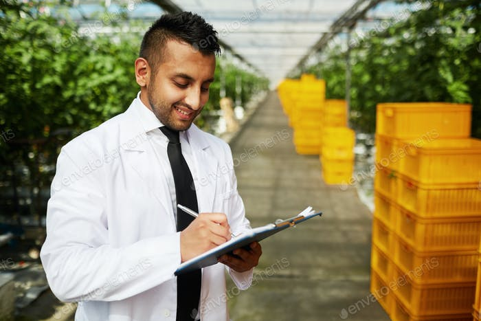 Middle-eastern scientist in greenhouse