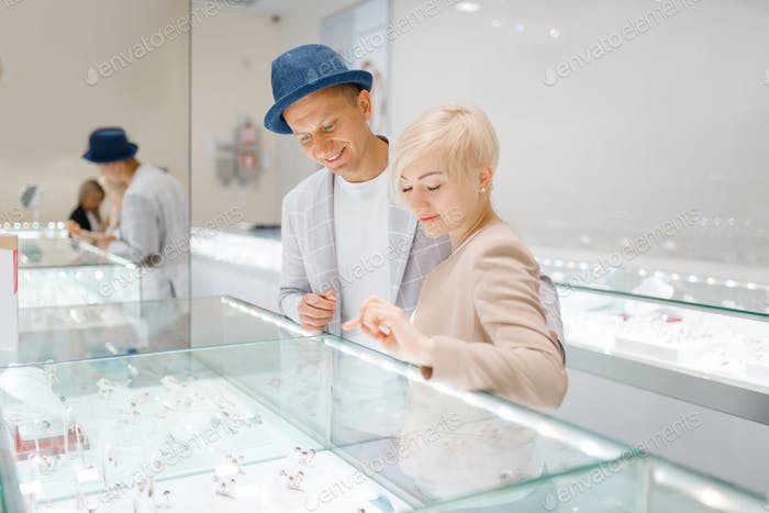 Love couple looking on jewels in jewelry store