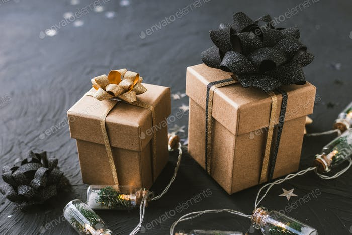 Weihnachtsgeschenke mit einer goldenen und schwarzen Schleife auf einem schwarzen Hintergrund.