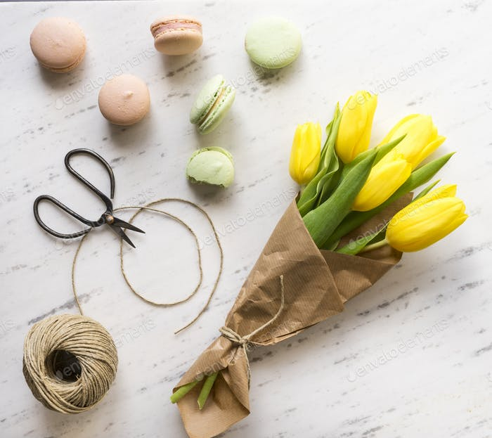 Flowers, macarons and scissors on marble background