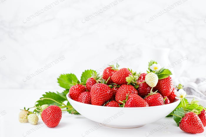 Strawberry on plate with twigs and leaves on white  background