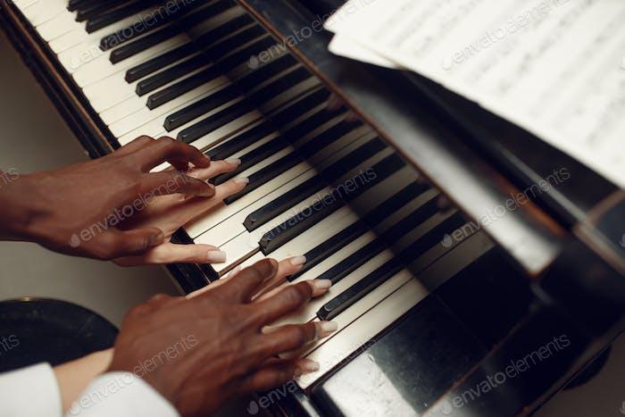 Ebony grand piano player hands on the keys