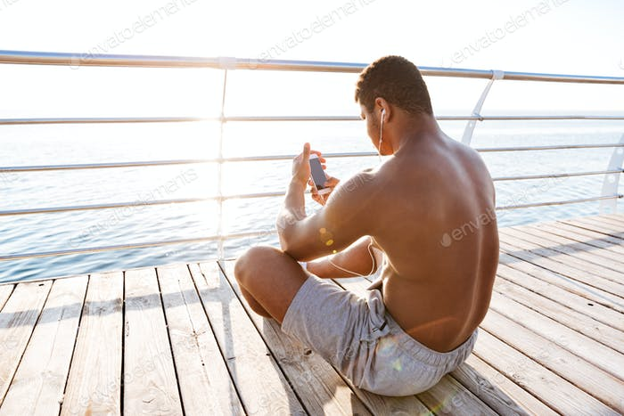 Afro american sports man resting after workout and listen music