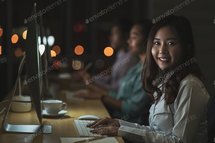 Portrait of Asian Female customer care service with business man smiling and working hard