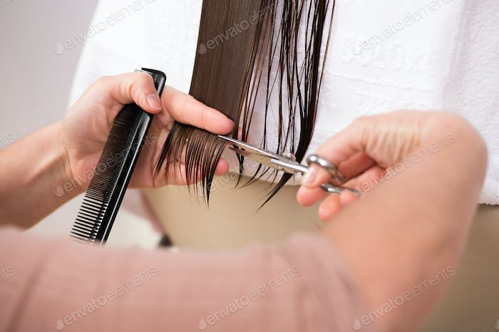 Hairdresser trimming the end of a ladies hair