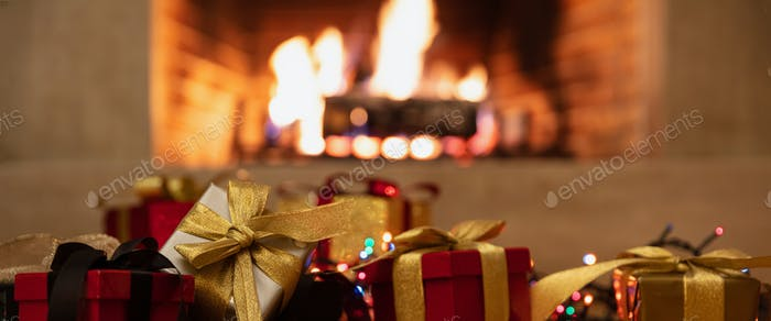 Christmas gifts and lights glowing, blur burning fireplace background