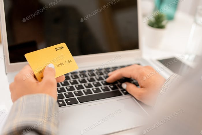 Modern businesswoman entering personal data from plastic card in front of laptop
