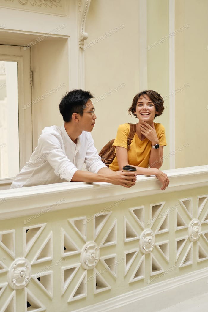 Young international students happily talking at break leaning on railing in corridor of university
