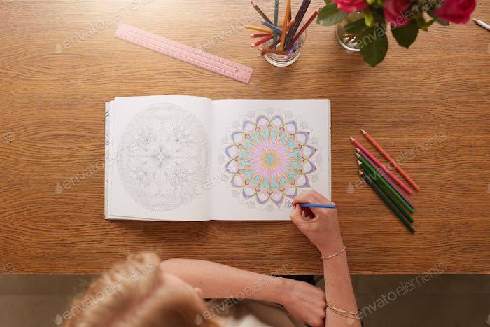 Woman drawing in adult colouring book