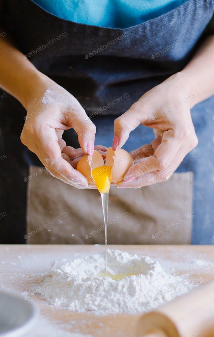 Baker trägt ein Ei auf Mehl