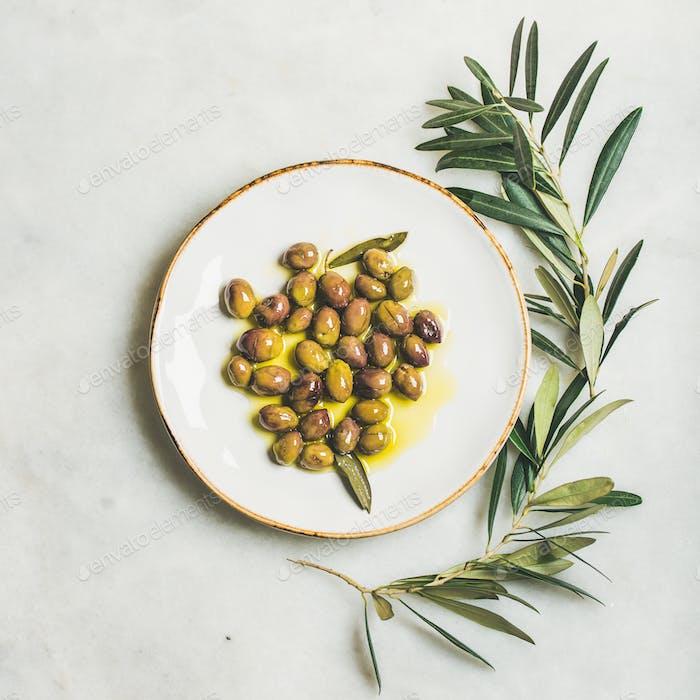 Pickled green Mediterranean olives in virgin olive oil, square crop