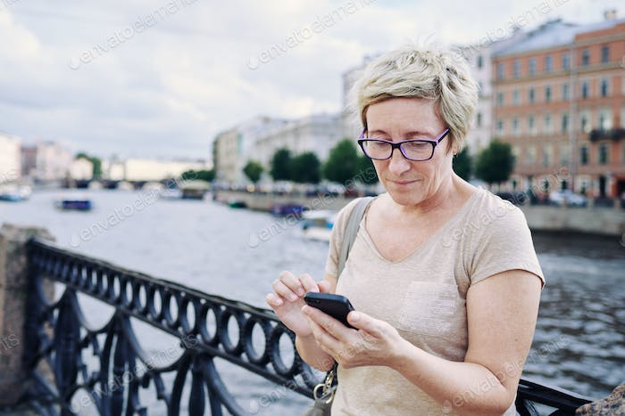 Aged woman browsing smartphone on embankment