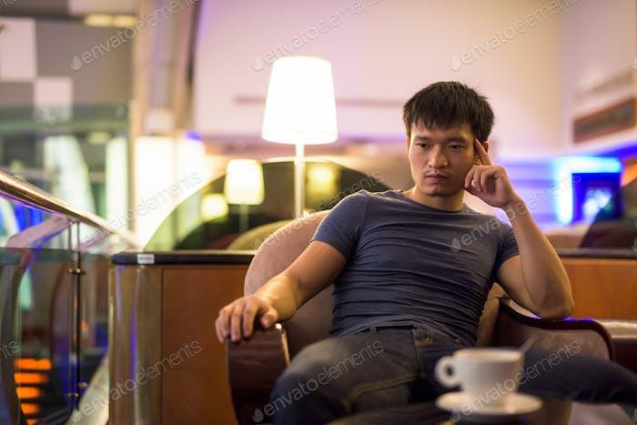 Porträt junger asiatischer Mann denken und sitzen in der Mall