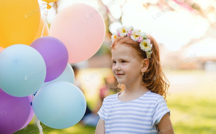 Small girl standing outdoors in garden, birthday celebration concept.
