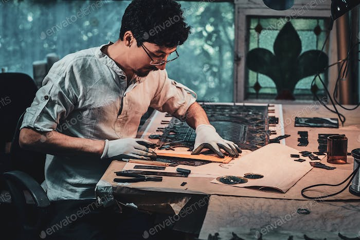 Focused restorer in glasses is counting right amount for stained glass