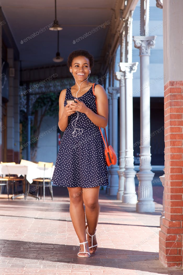 smiling young black woman walking with cellphone and earphones