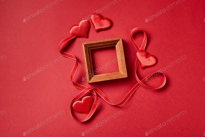 Wooden fame and Valentines day hearts and decorations on red background
