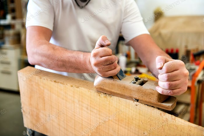 Carpenter planing the surface of a panel of wood