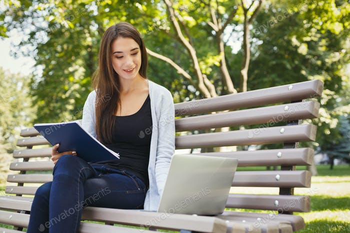 Smiling student girl sitting in park using laptop