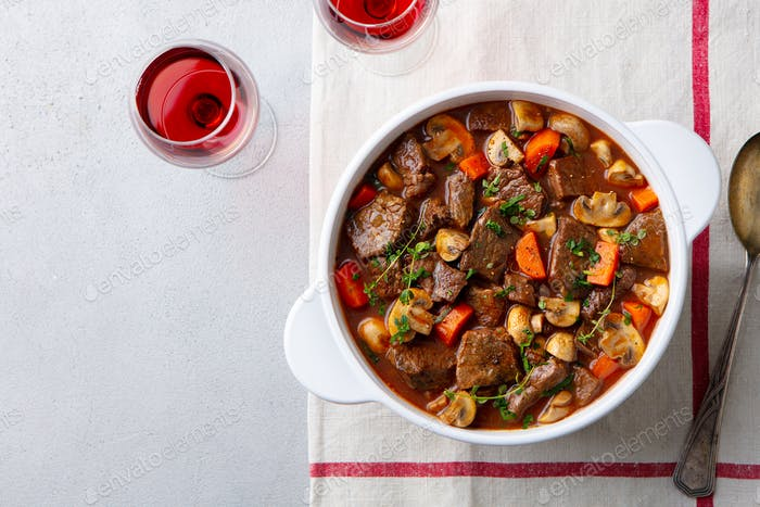 Beef Bourguignon Stew with Vegetables and Red wine. Grey Background. Top view.