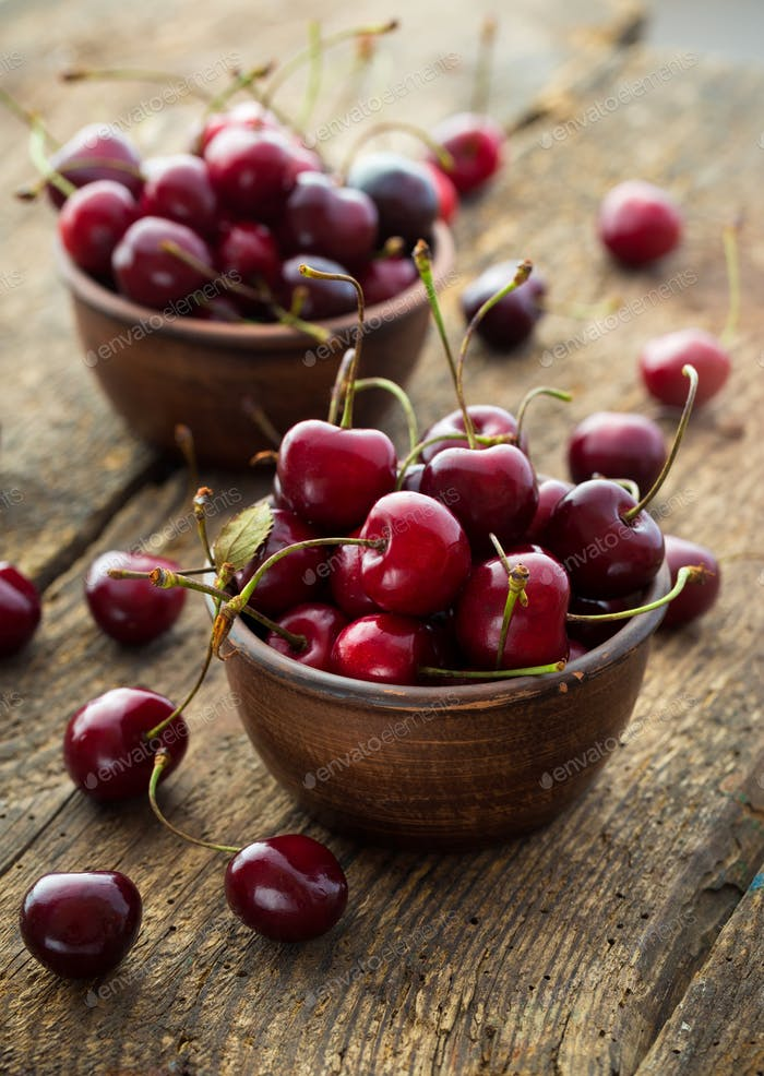 Ripe cherries in a clay bowl on wooden background